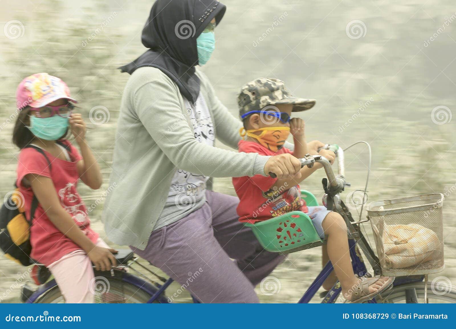 Moder med hennes två barn till och med en utbrottmontering Kelud för vulkanisk aska