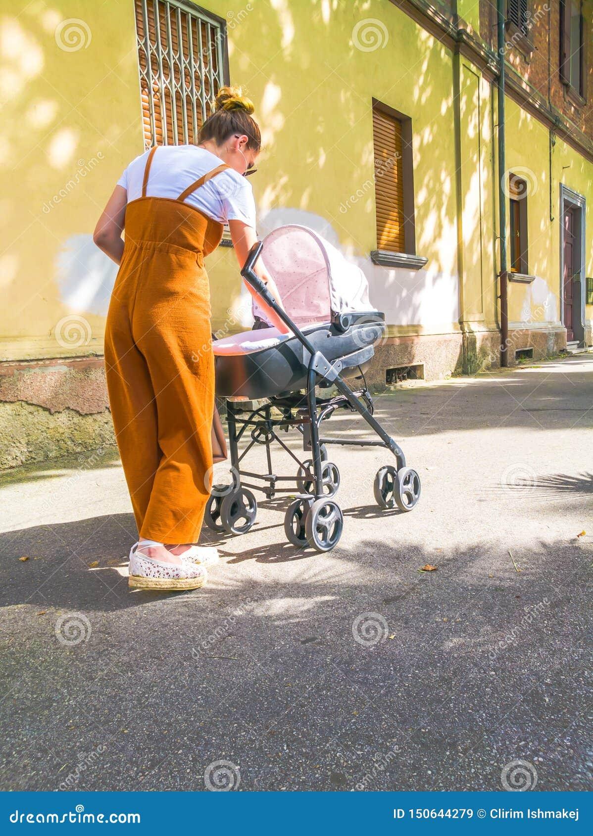 Moder med sittvagnen i stad