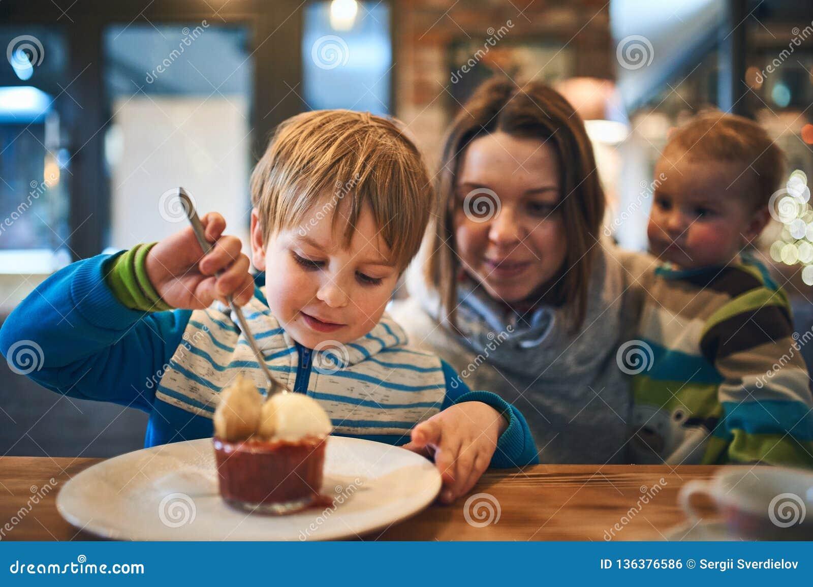 Moder med två ungar i väntande på beställning för kafé