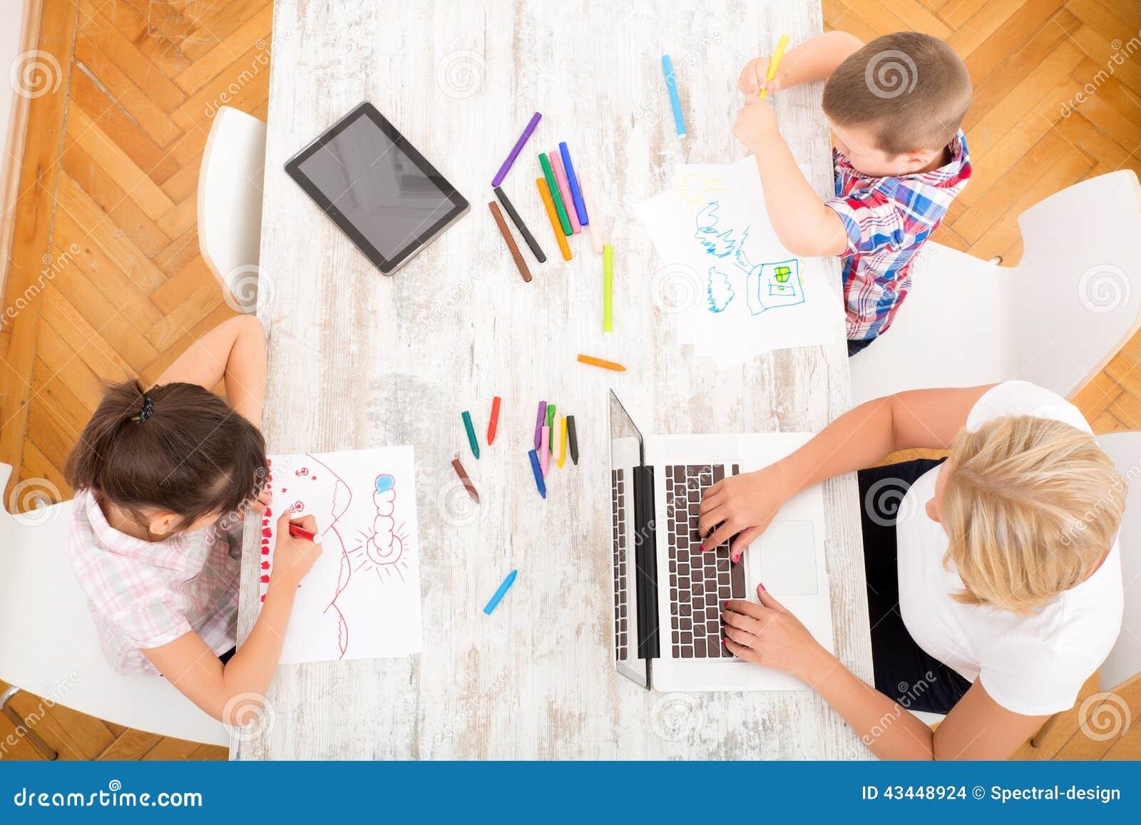 Moder och barn med en hemmastadd bärbar dator