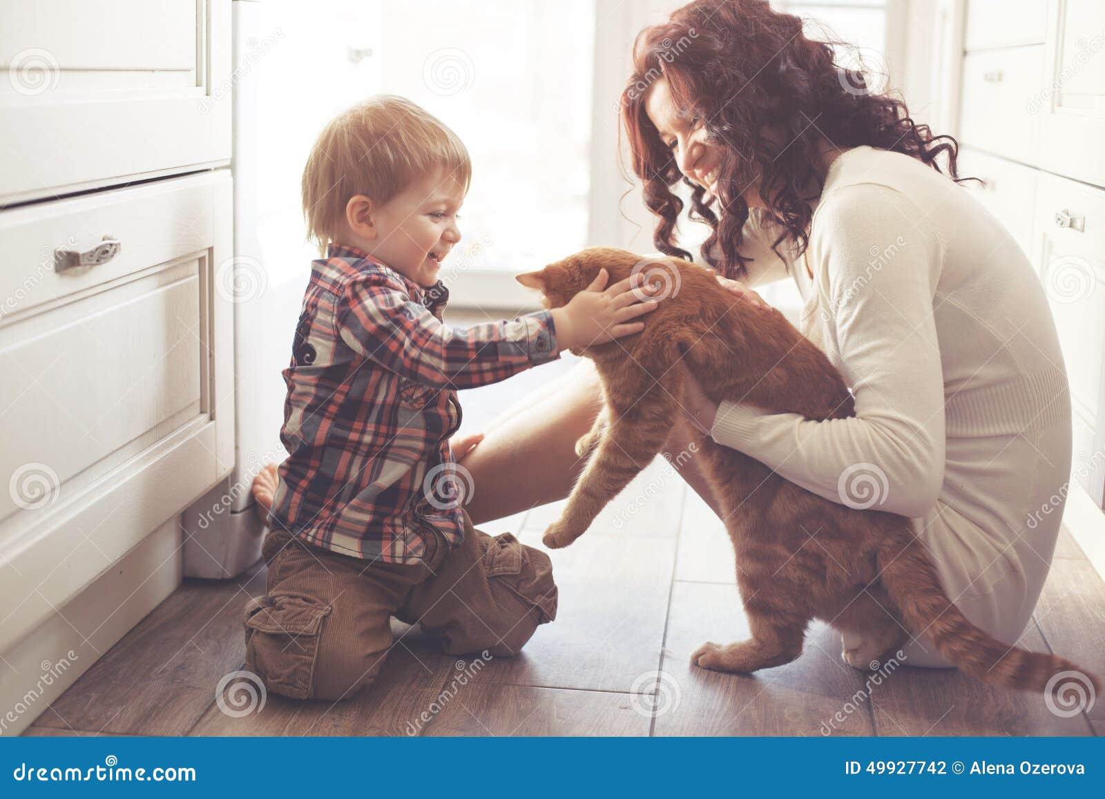 Moder och barn som spelar med katten