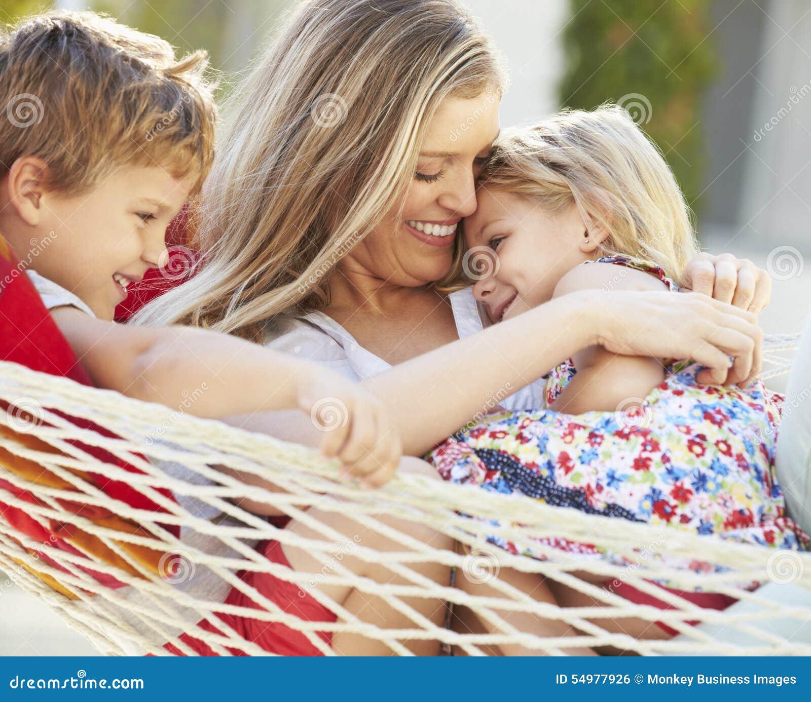 Moder och barn som tillsammans kopplar av i trädgårds- hängmatta