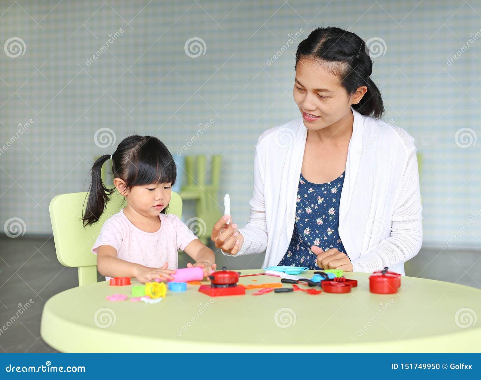 Moder- och barnflicka som sitter på tabellen och den konstgjorda frukten för lekar