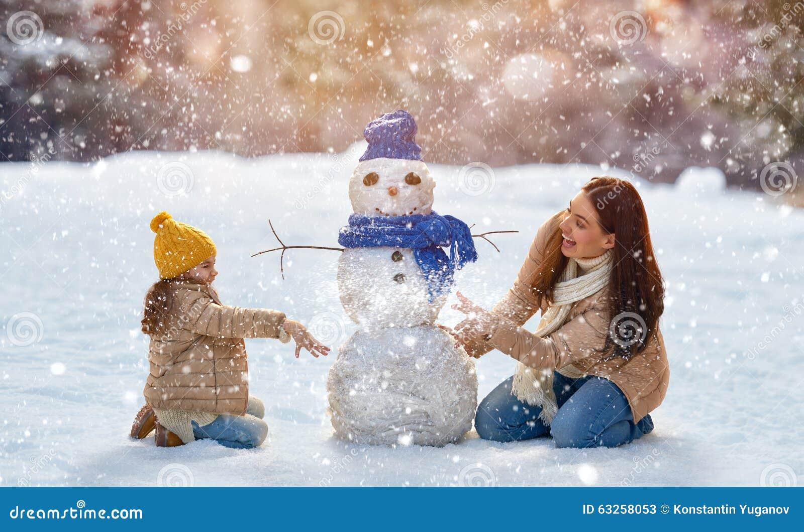 Moder- och barnflickan på en vinter går i natur