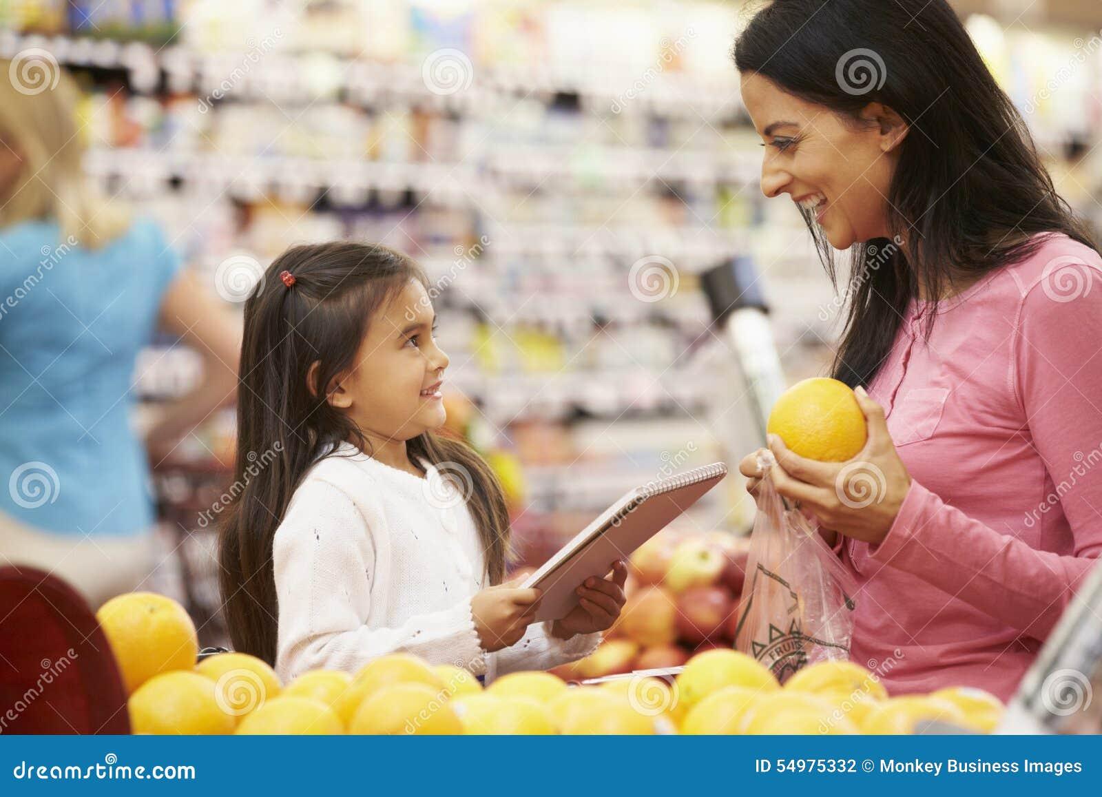 Moder och dotter på frukträknaren i supermarket med listan