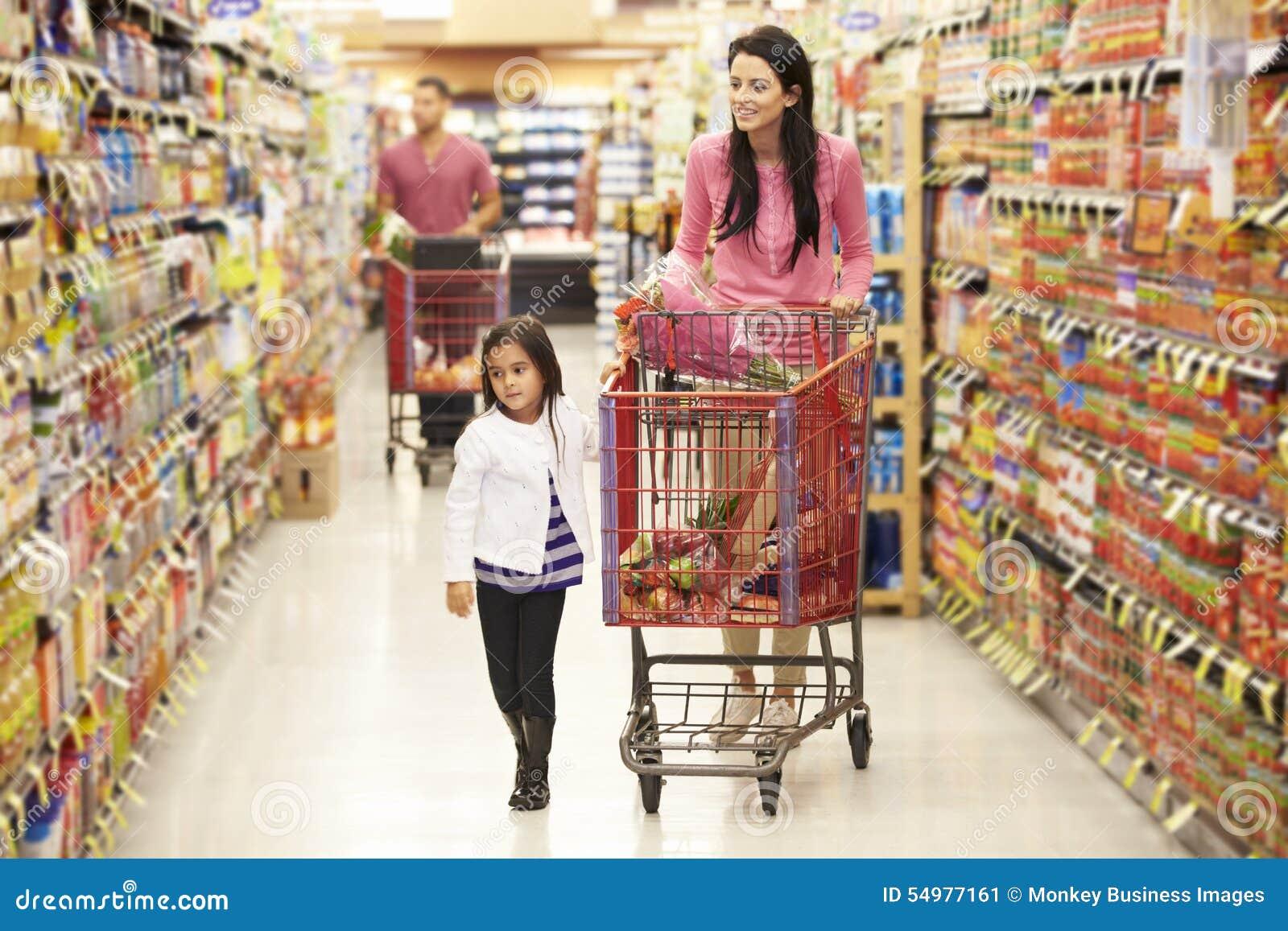 Moder och dotter som går ner livsmedelsbutikgången i supermarket