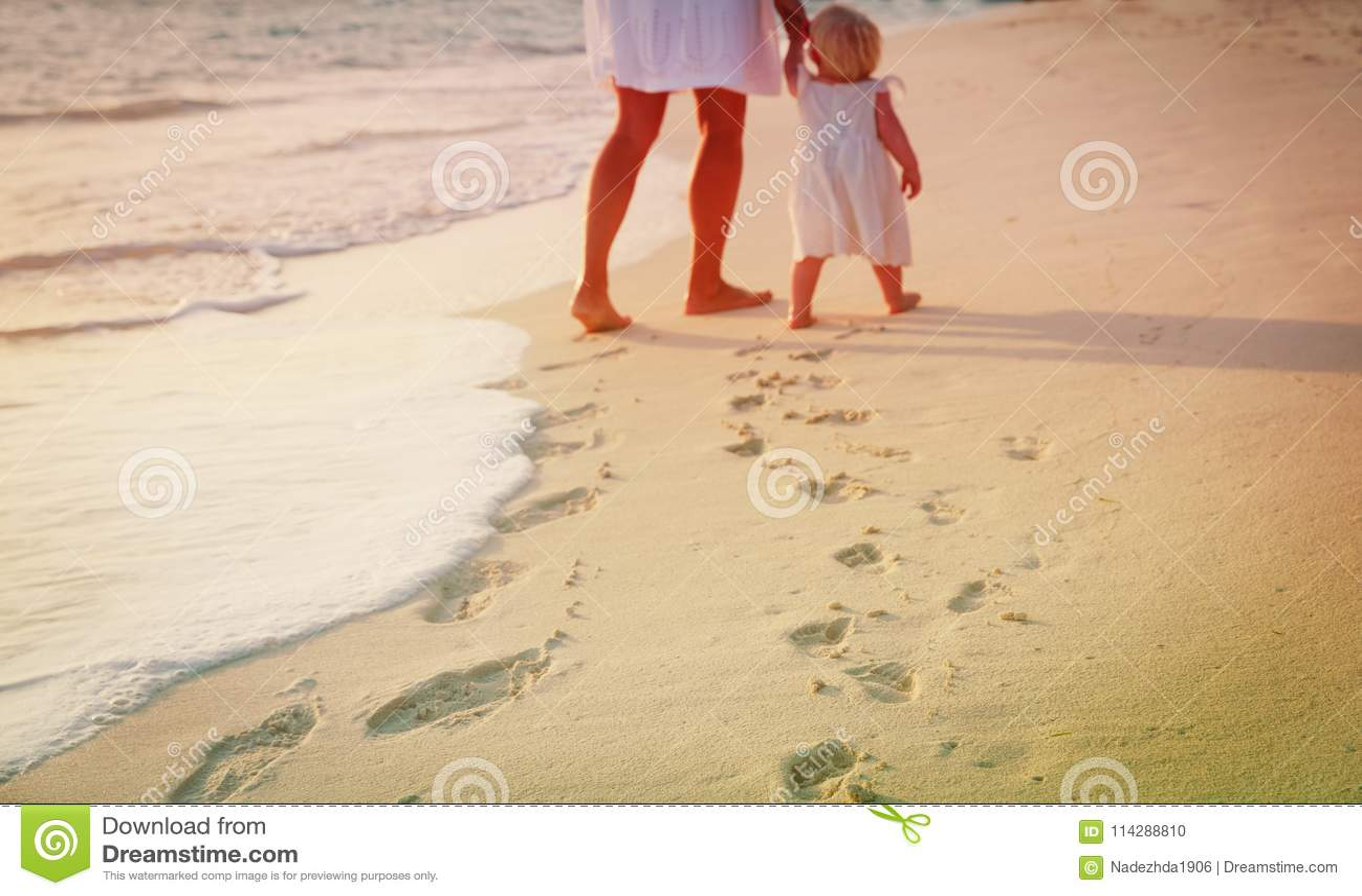 Moder och dotter som går på stranden som lämnar fotspår i sand
