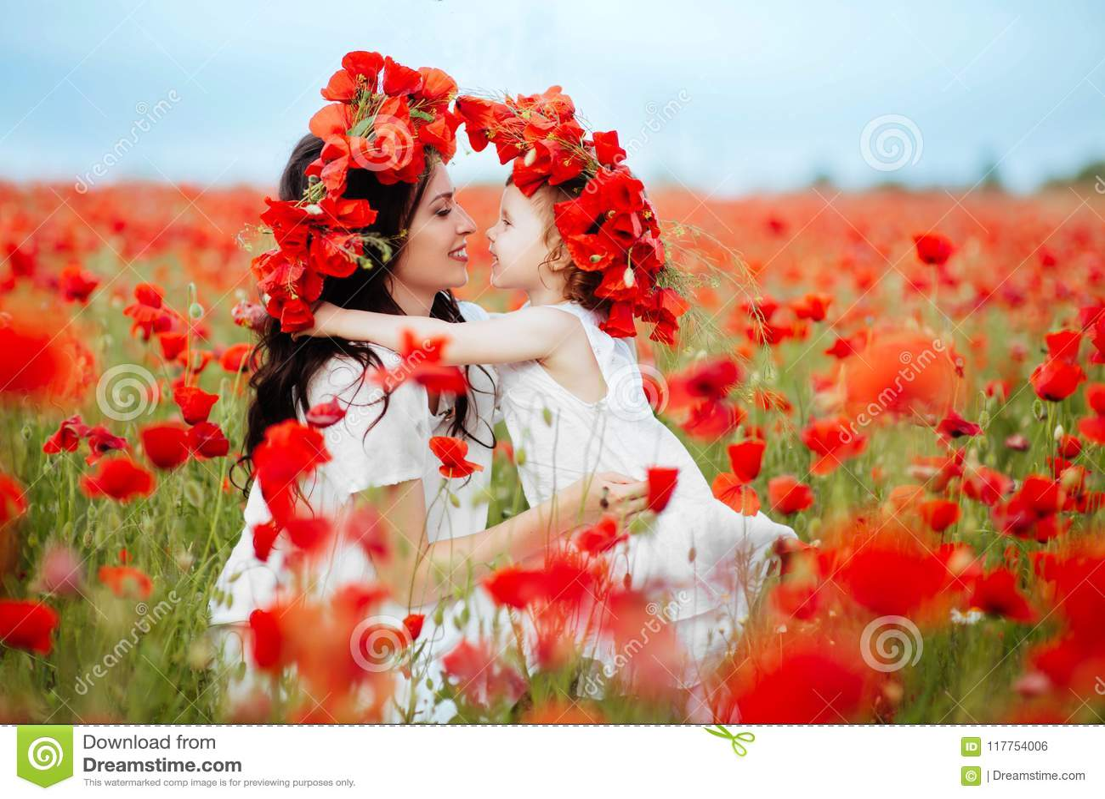 Moder och dotter som spelar i blommafält