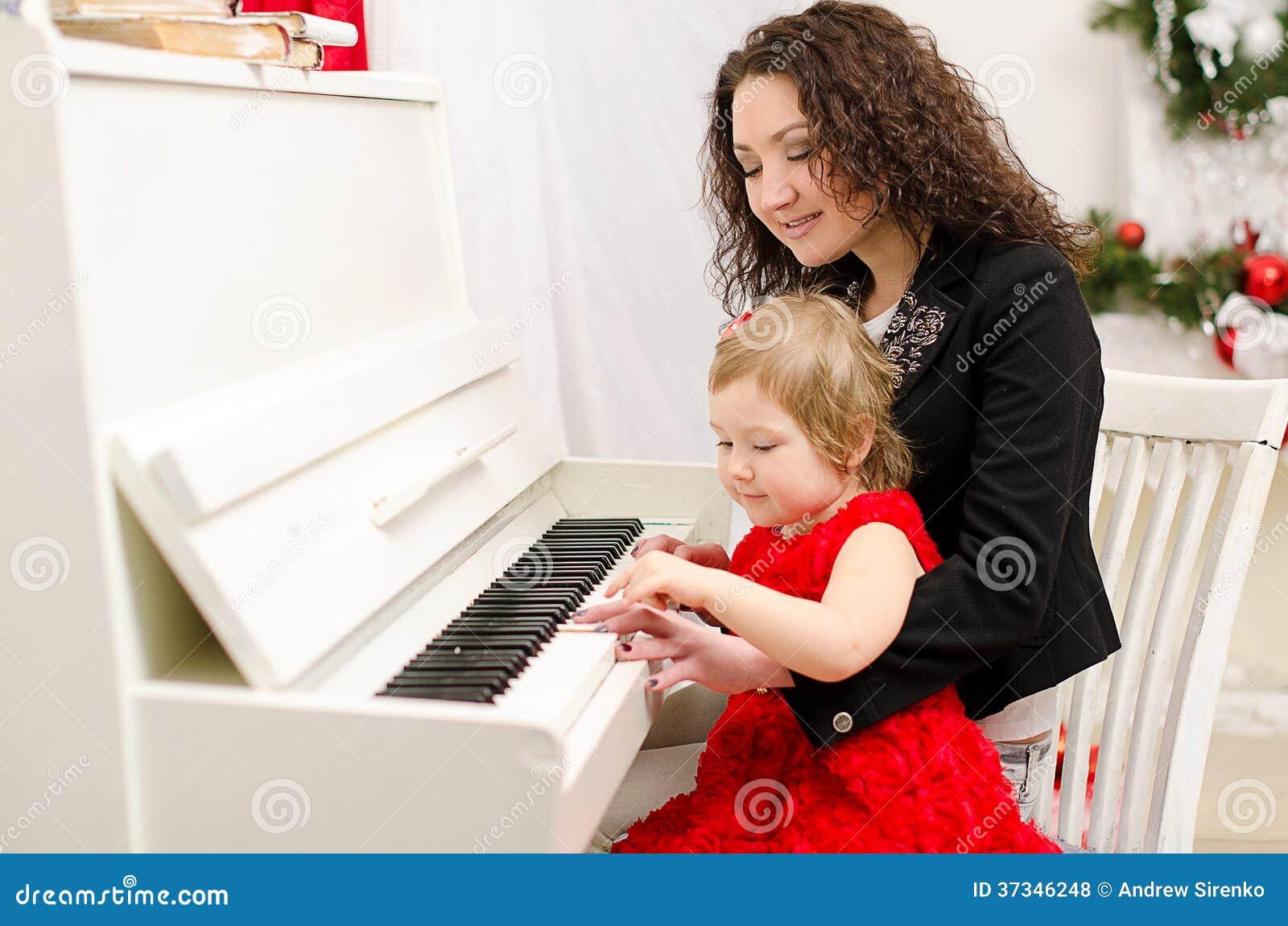 Moder och dotter som spelar på det vita pianot