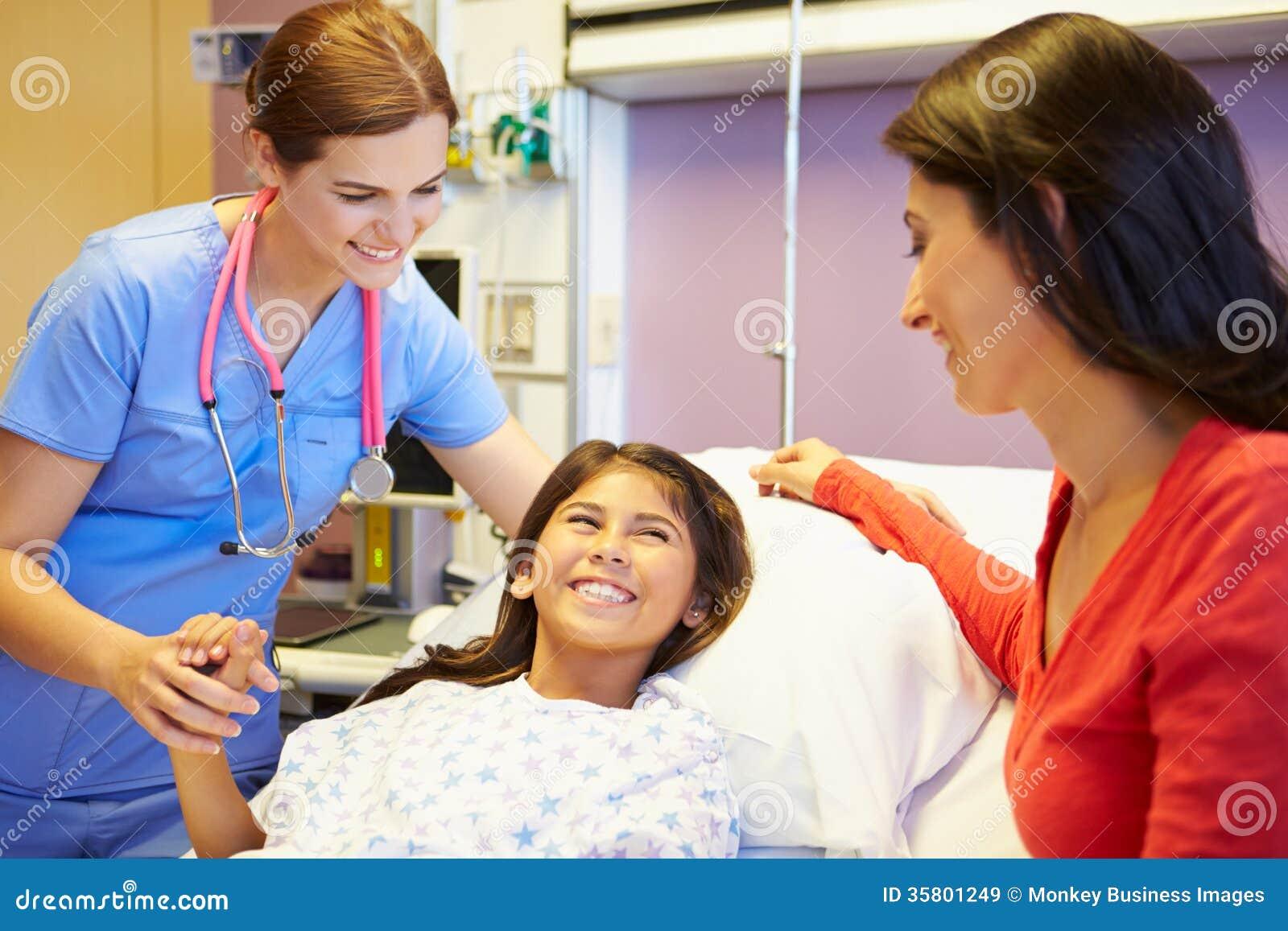 Moder och dotter som talar till den kvinnliga sjuksköterskan In Hospital Room