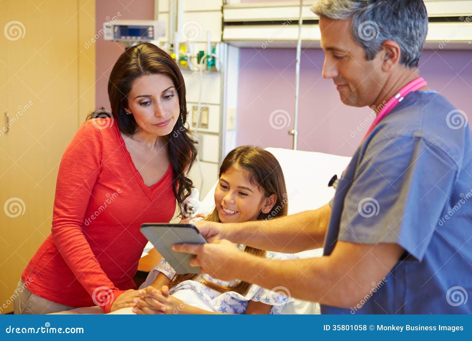 Moder och dotter som talar till konsulenten In Hospital Room