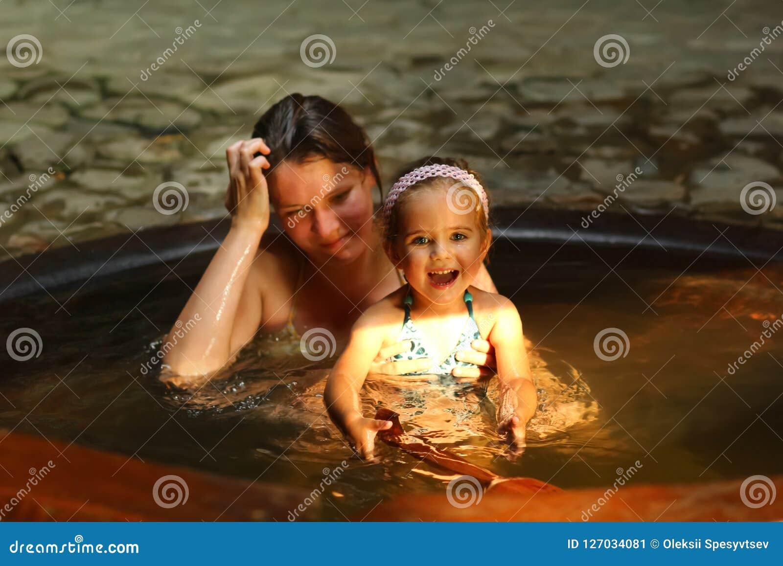 Moder och dotter som tar brunnsort det termiska badet