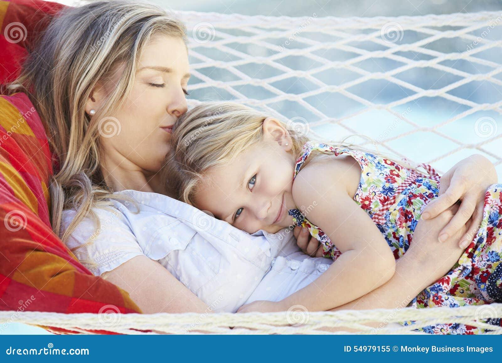 Moder och dotter som tillsammans kopplar av i trädgårds- hängmatta