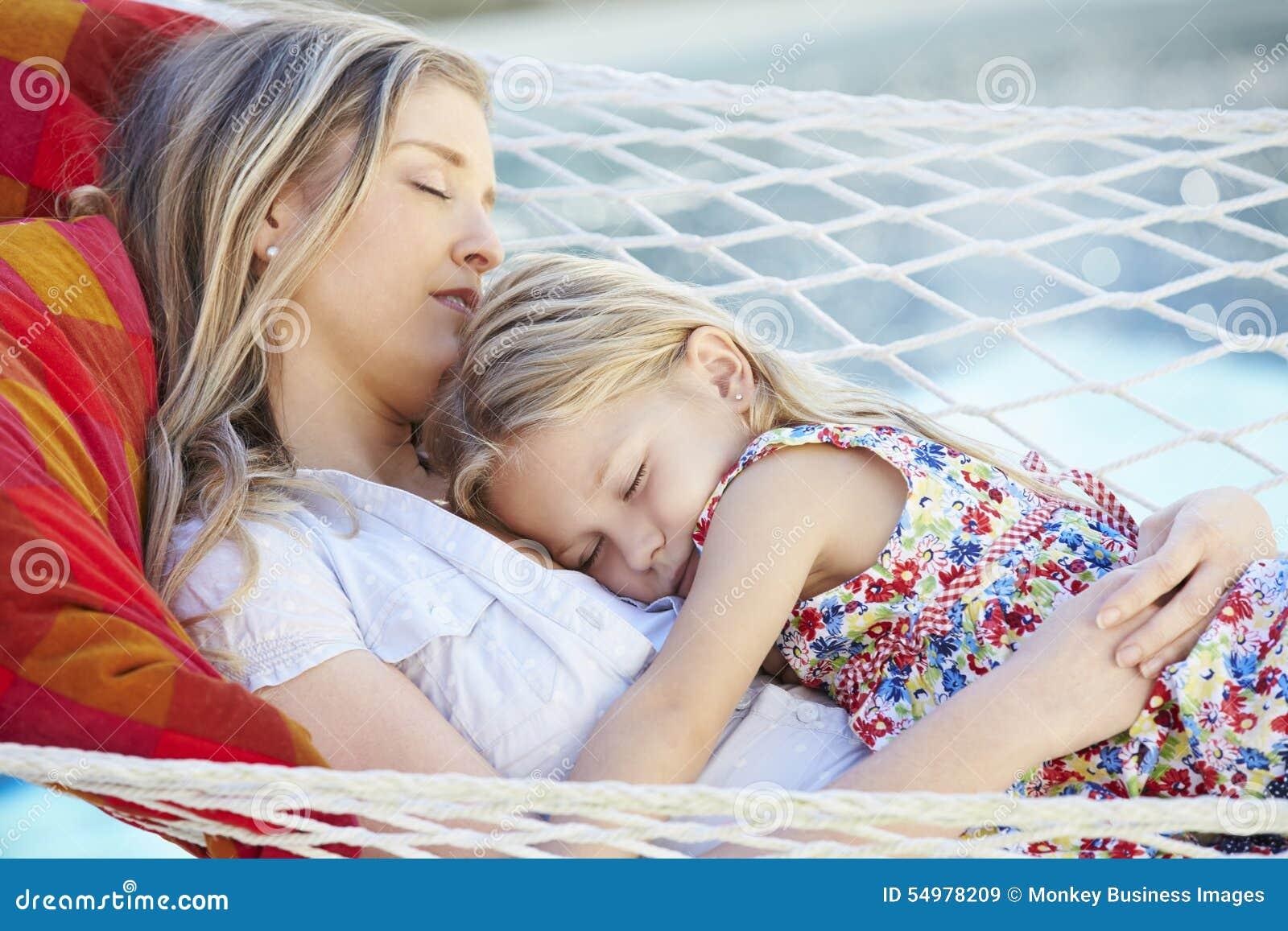 Moder och dotter som tillsammans sover i trädgårds- hängmatta
