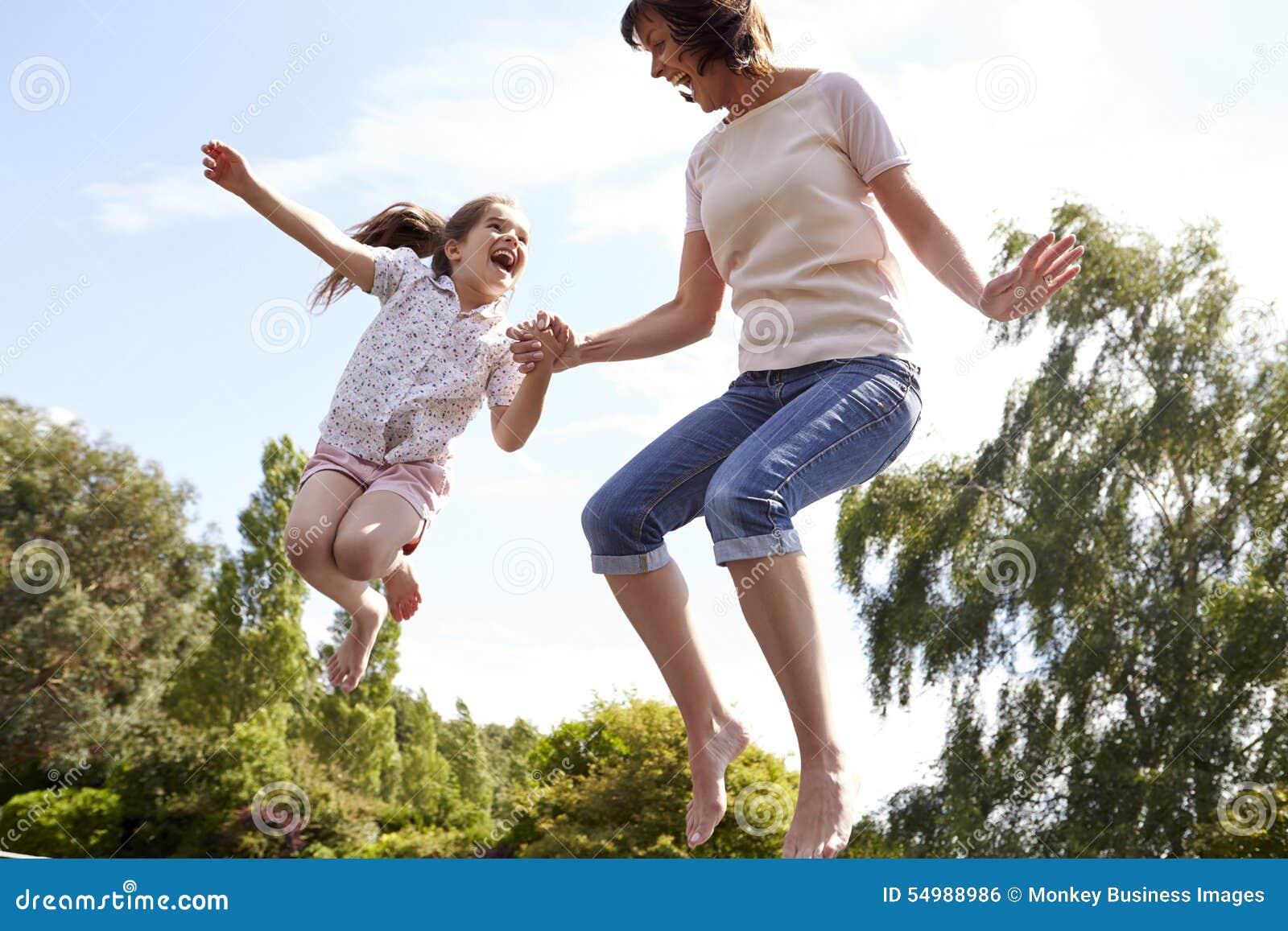 Moder och dotter som tillsammans studsar på trampolinen