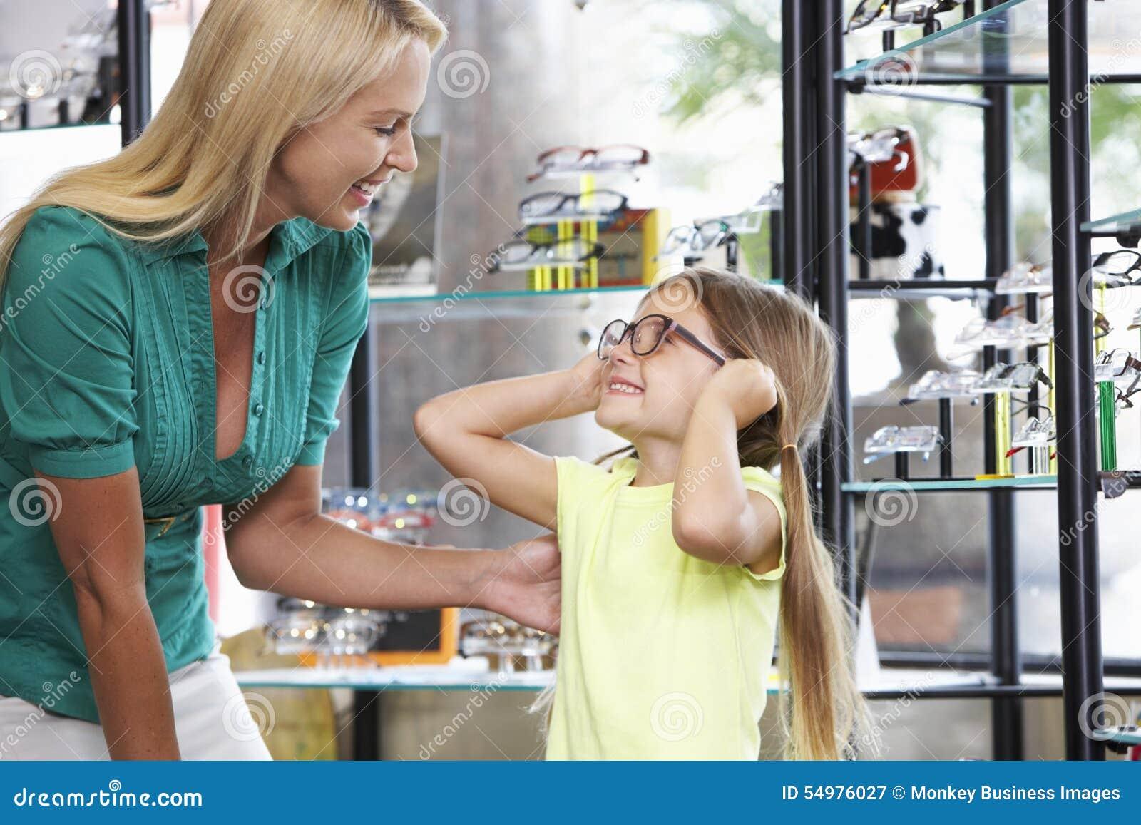 Moder och dotter som väljer exponeringsglas i optiker
