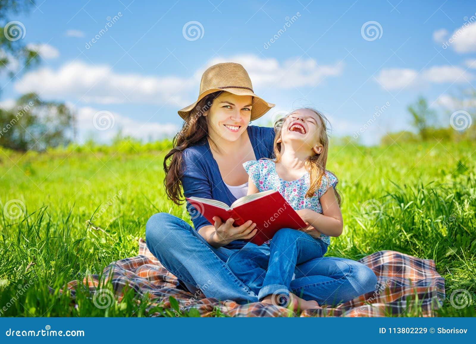 Moder- och dotterläsebok på grön sommaräng