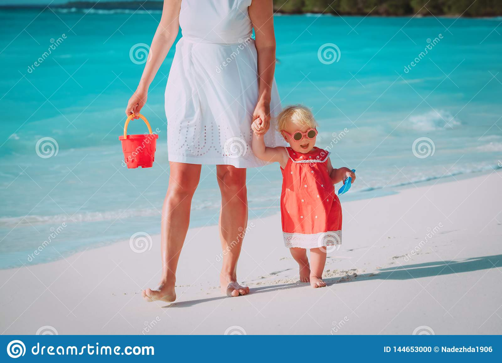 Moder och gullig liten dotter som g?r p? stranden