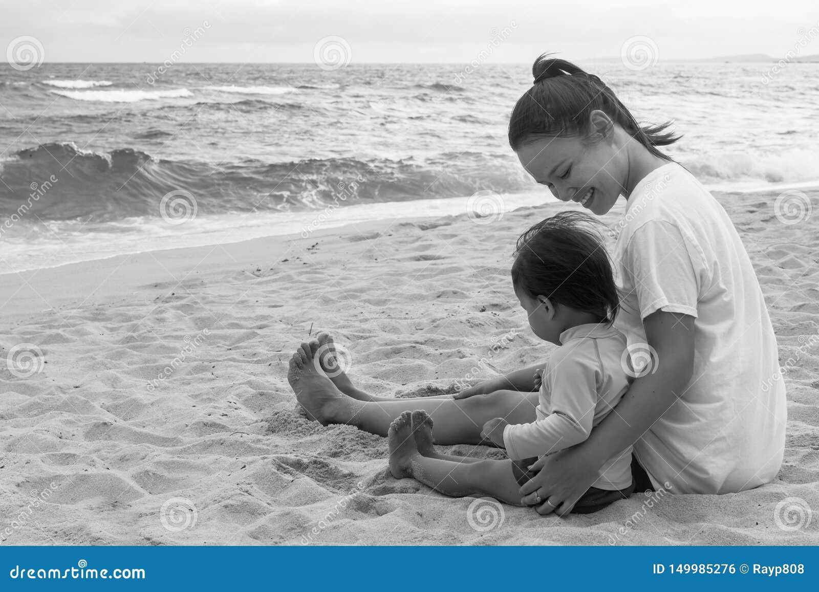 Moder och hennes barn som spelar på stranden tillsammans utomhus