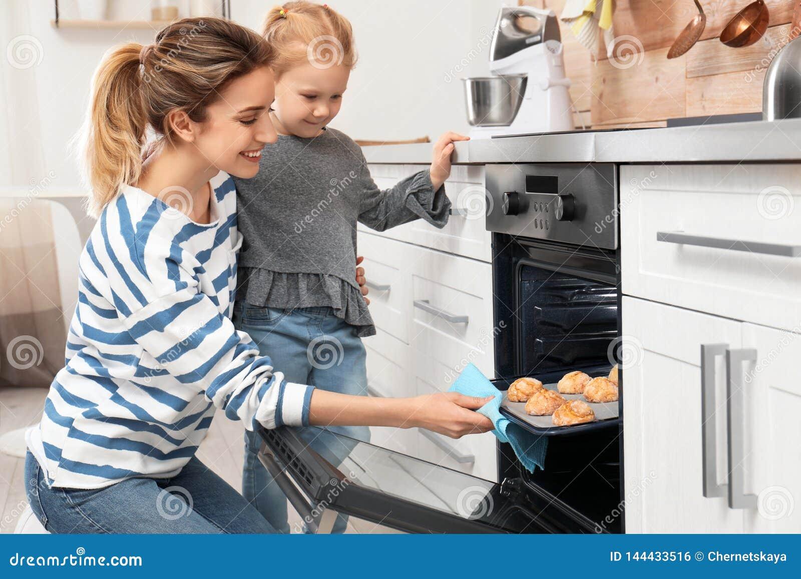 Moder och hennes dotter som ut tar kakor fr?n ugnen