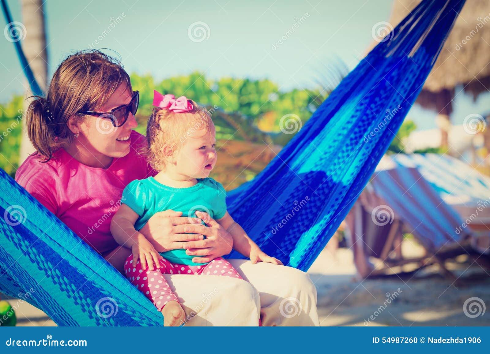 Moder och liten dotter som kopplas av i hängmatta