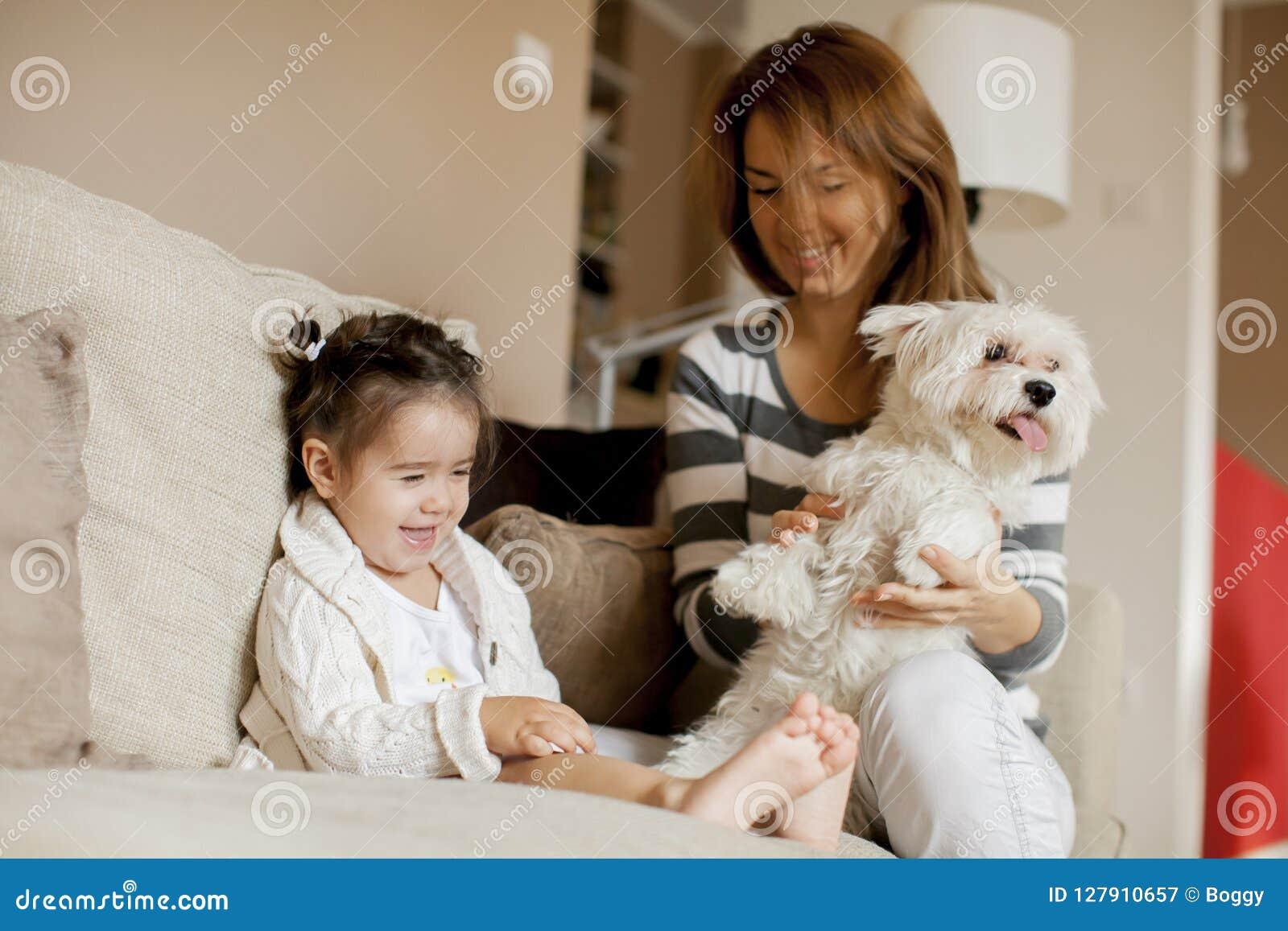 Moder och liten flicka med hunden i rummet