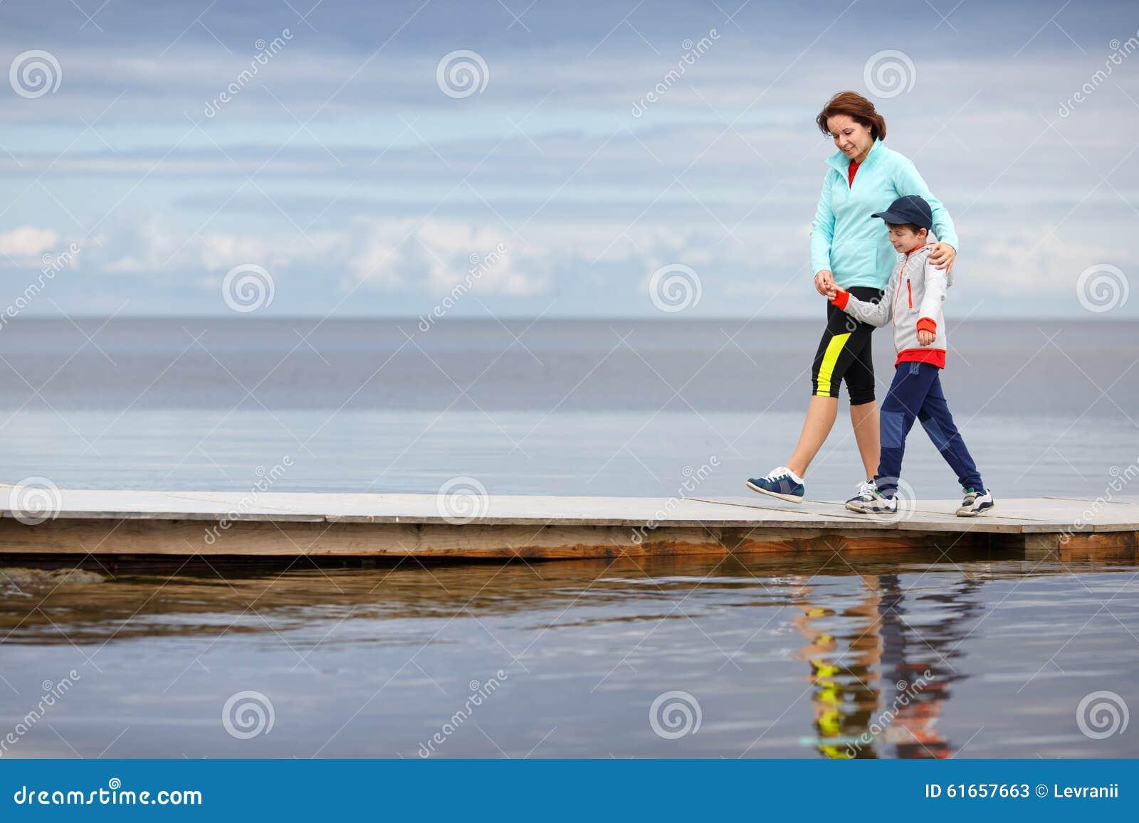 Moder och liten son som tillsammans går på trä