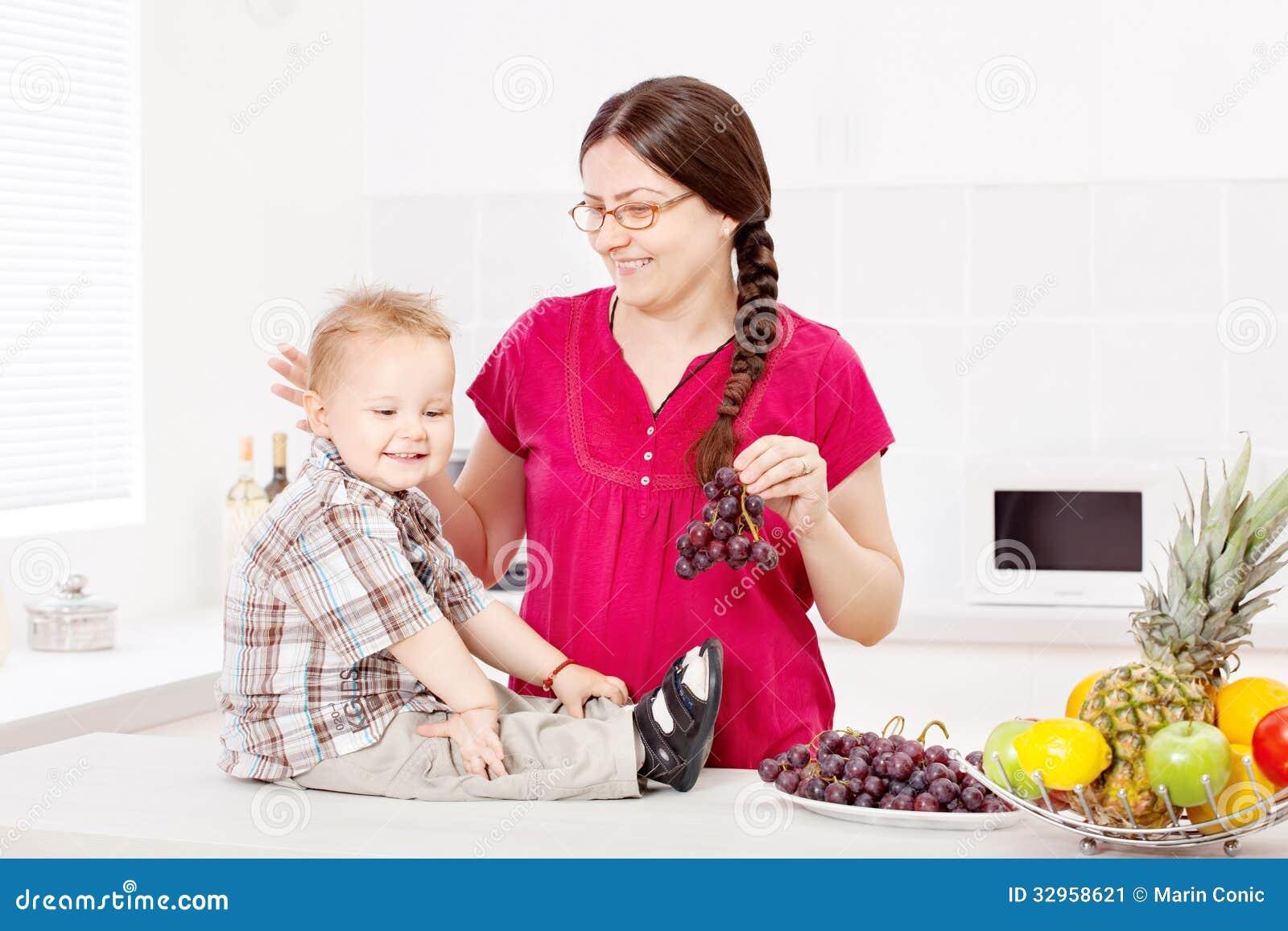 Moder och son med frukter i köket