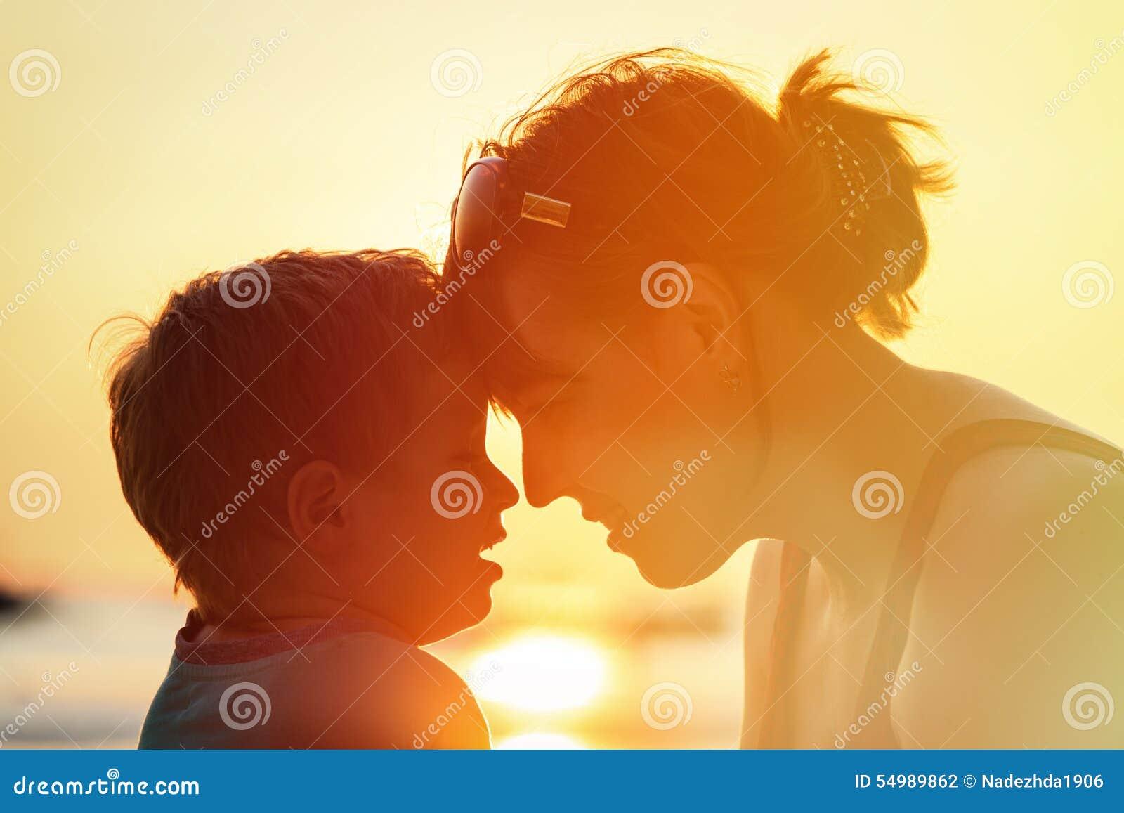 Moder och son på solnedgångstranden