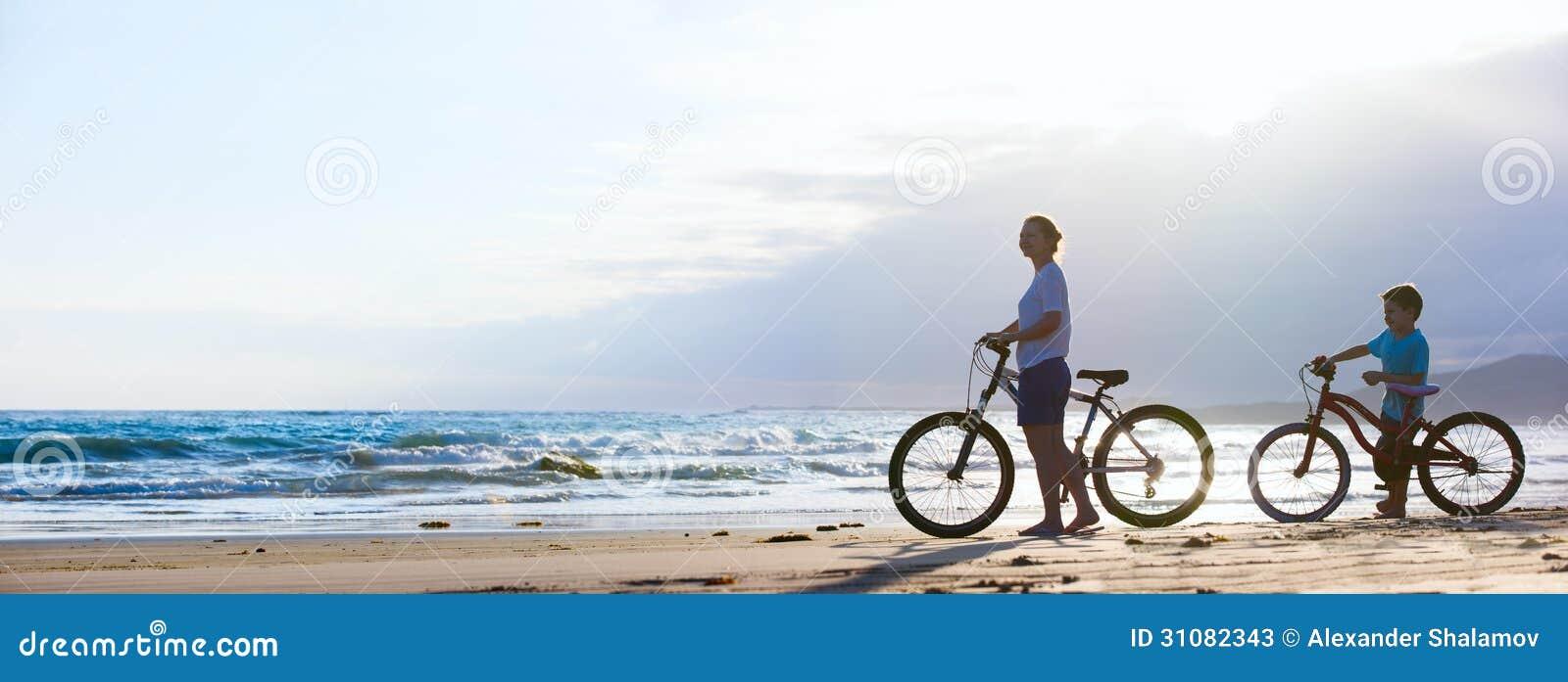 Moder och son som cyklar på stranden