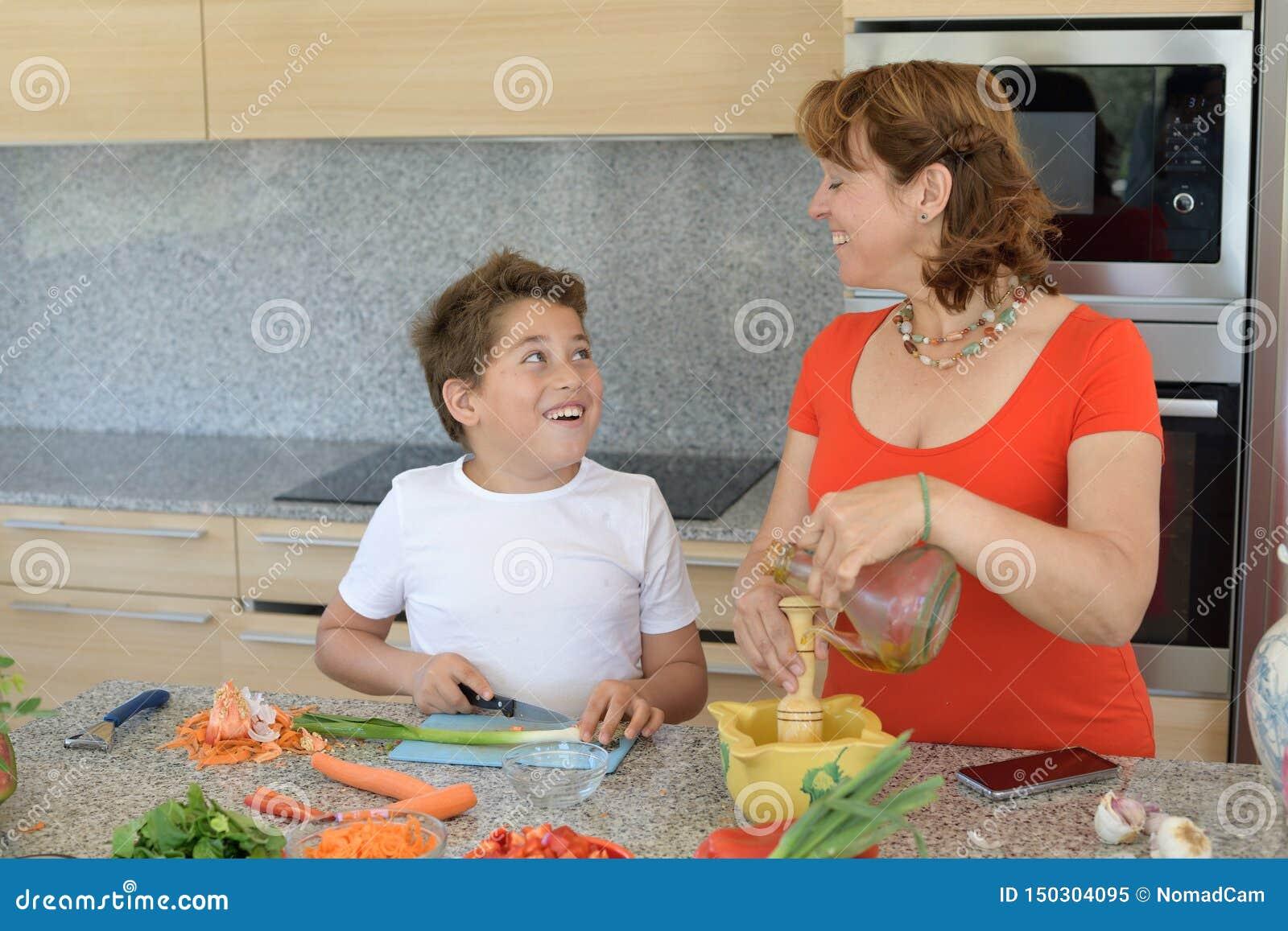 Moder och son som förbereder lunch och leenden Sonen klipper vitlök