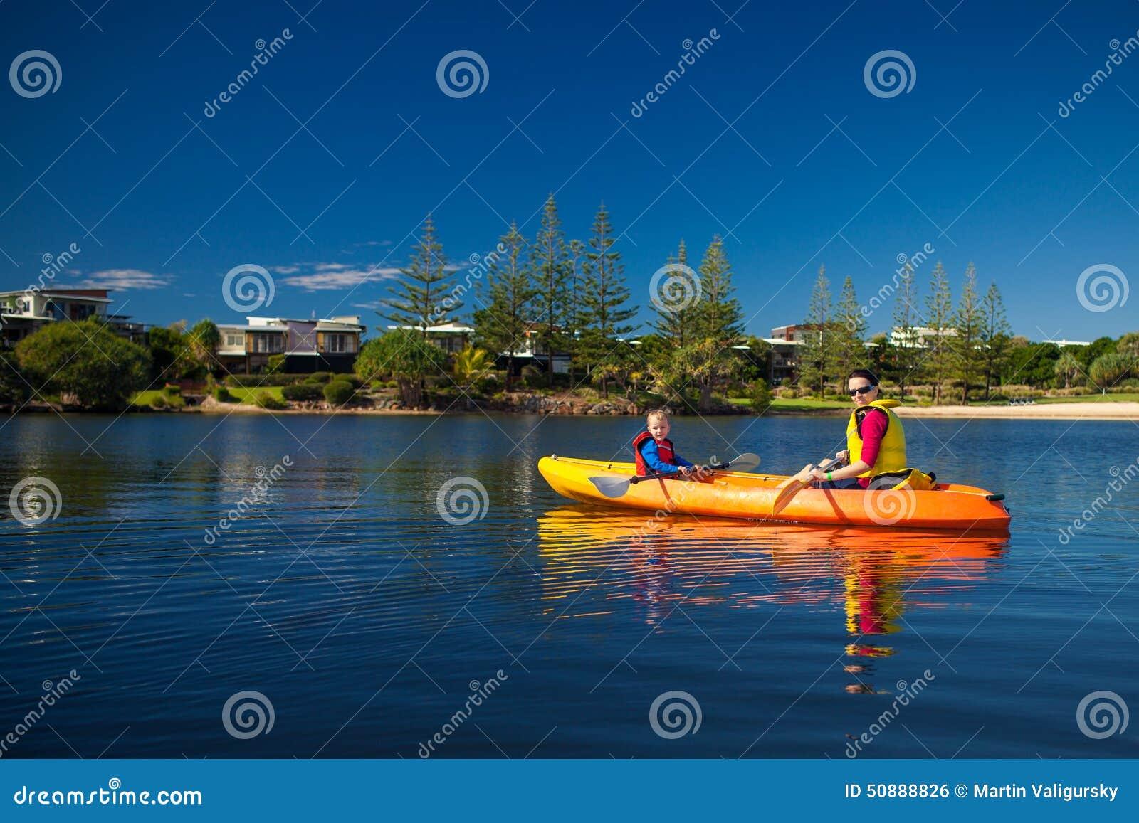 Moder och son som kayaking i en liten sjö