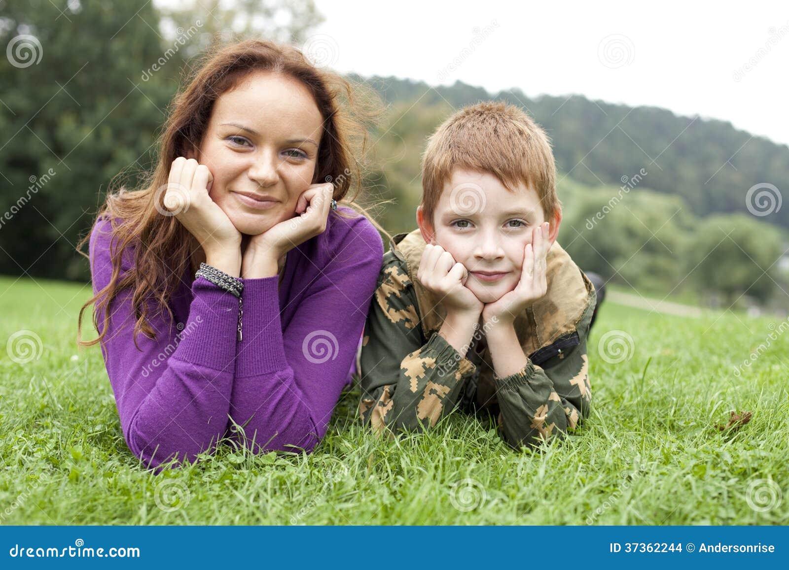 Moder och son som ligger på det gröna gräset