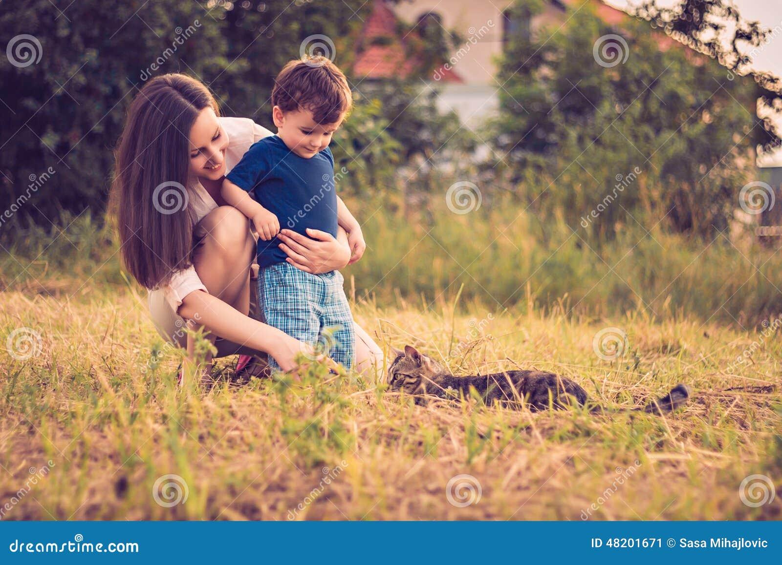 Moder och son som spelar med katten