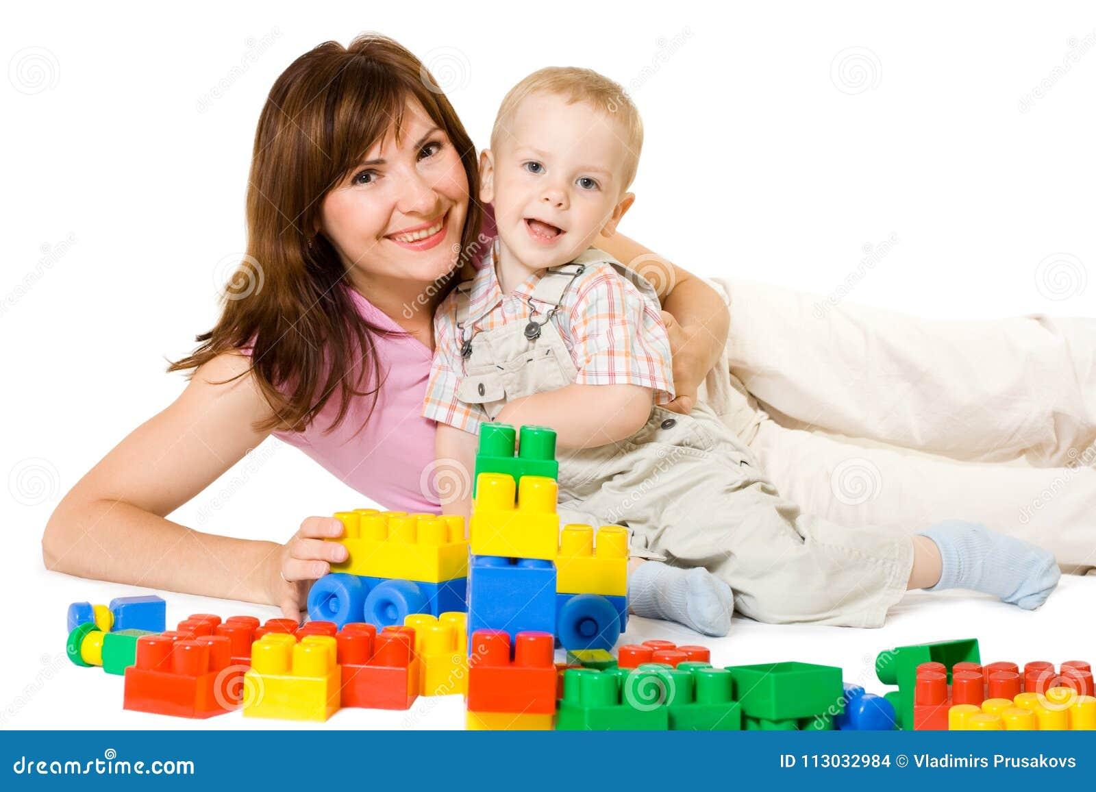 Moder och unge som spelar färgrika leksaker för byggnadskvarter, lycklig familj