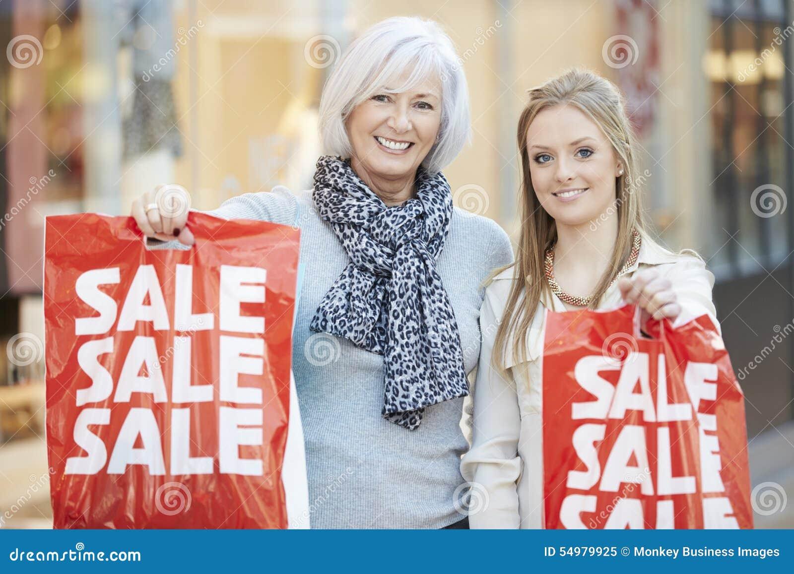 Moder- och vuxen människadotter i shoppinggalleria tillsammans