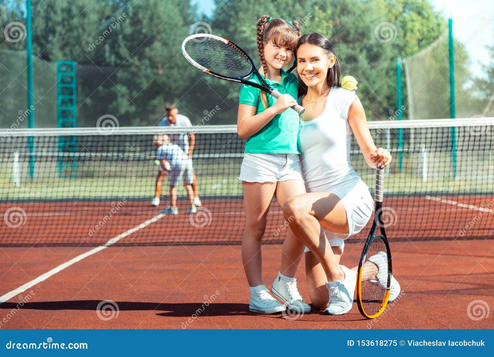 Moder som i huvudsak ler, innan att spela tennis med dottern