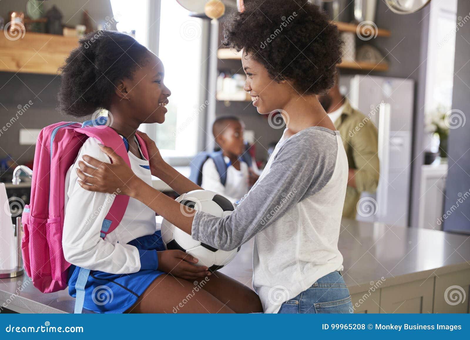 Moder som säger farväl till dottern, som hon lämnar för skola