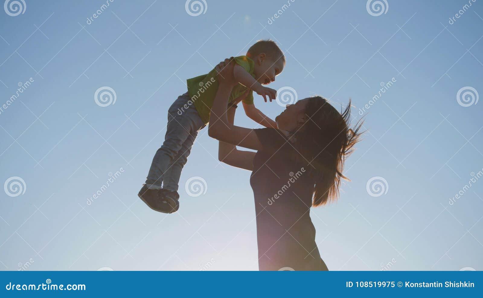 Moder som spelar med det lilla barnet på solnedgången - kast sonen