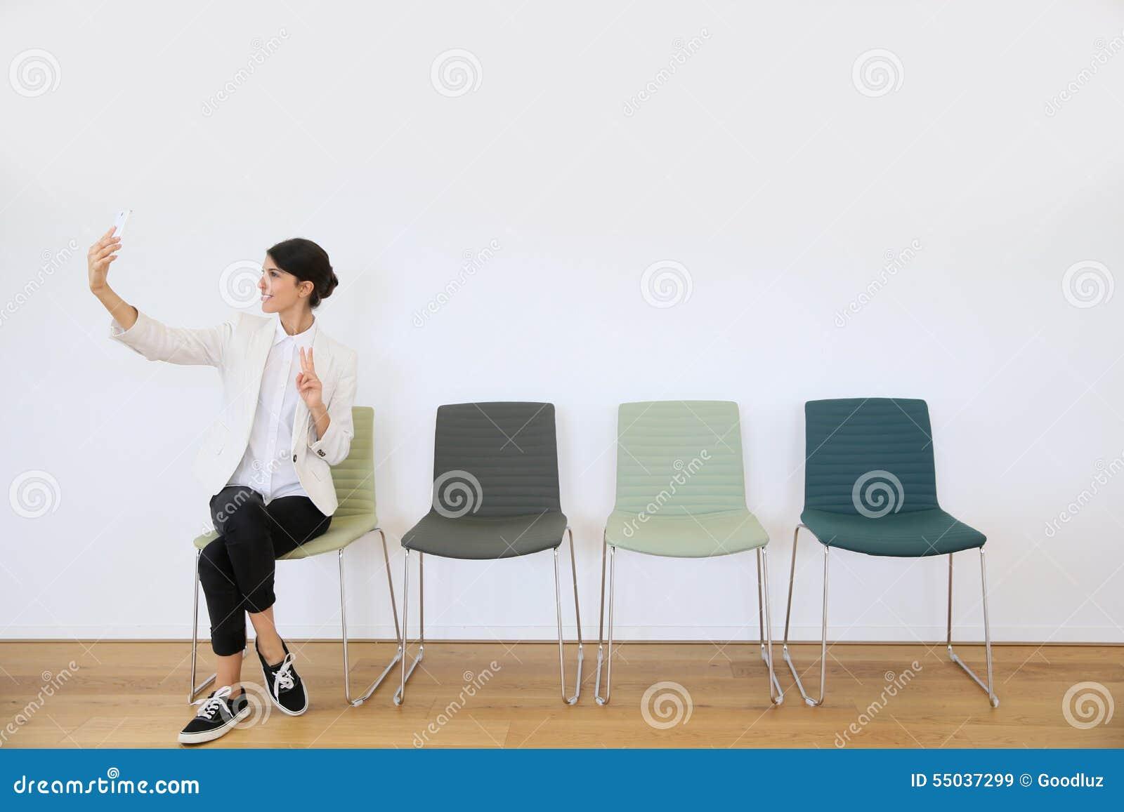 Moderiktig flicka som tar selfie i väntande rum