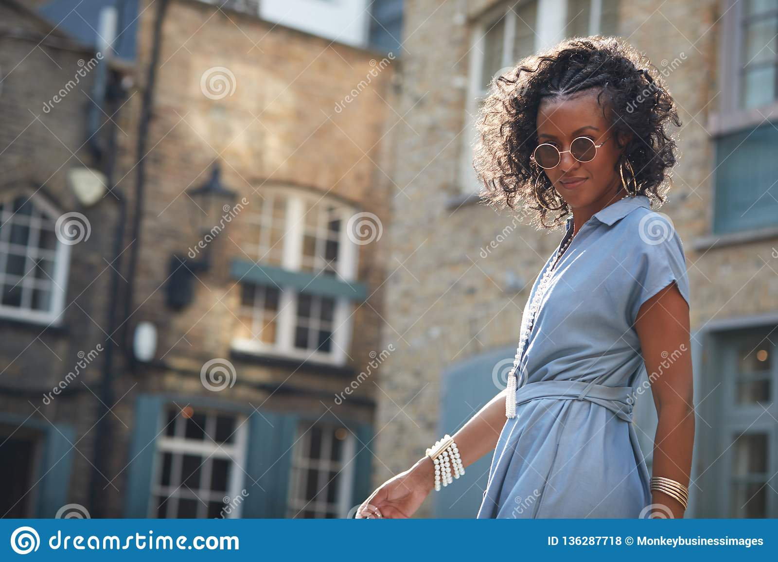 Moderiktig kvinna i blå korkad muffklänning och solglasögon