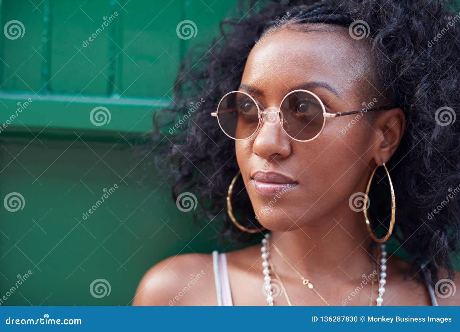 Moderiktig ung kvinna i camisole och solglasögon och smycken