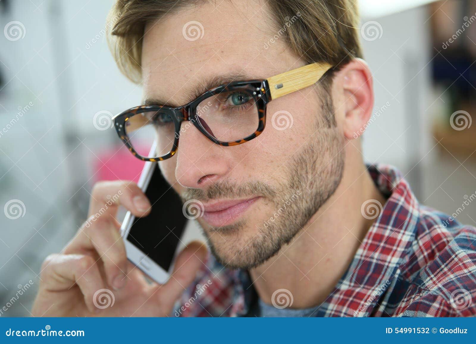 Moderiktig ung man som talar på telefonen