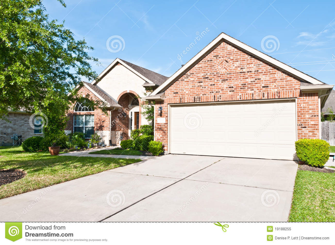 Front view of contemporary one story brick and stone house garage and driveway in american suburban neighborhood
