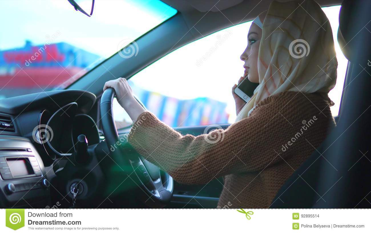 A Modern Arabic Woman Is Talking On The Phone, Driving In
