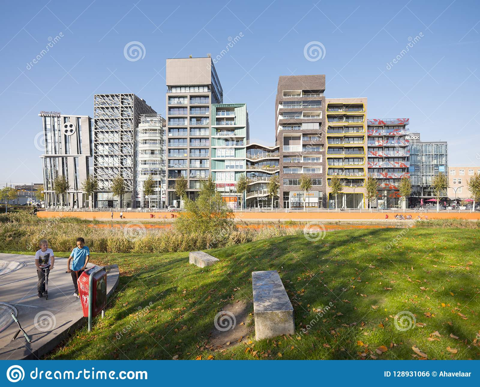Lelystad, Netherlands, 10 oktober 2018: modern architecture in dutch city  lelystad capital of flevoland in the netherlands and young boys with  scooters