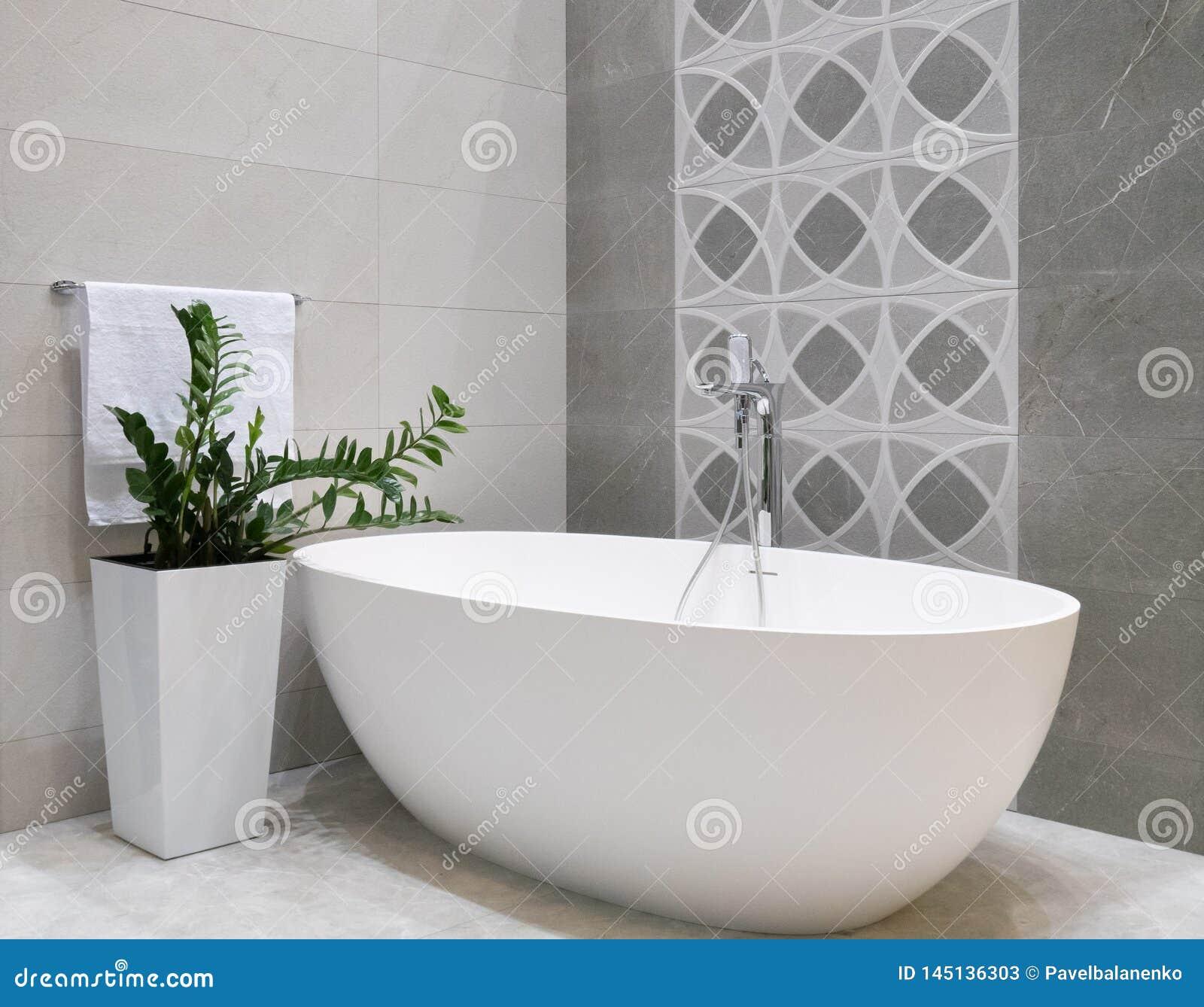 Modern badkamers binnenlands ontwerp met witte steenbadkuip, grijze tegelsmuur, ceramische bloempot met groene installatie en han