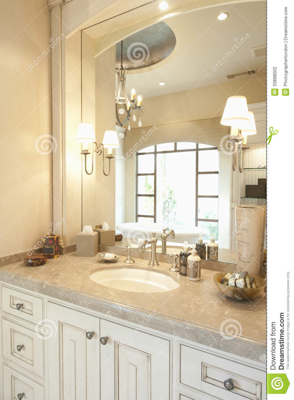 Marble topped cream bathroom with window reflected in mirror