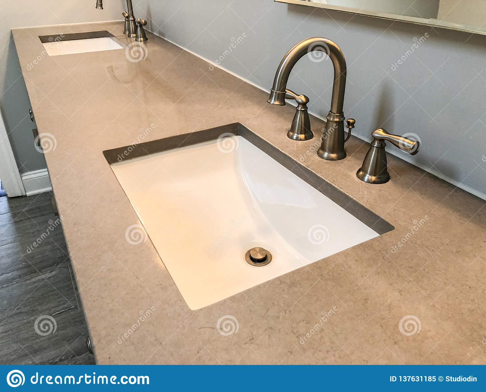 Modern bathroom with quartz countertop, two sinks and faucets with stone floor