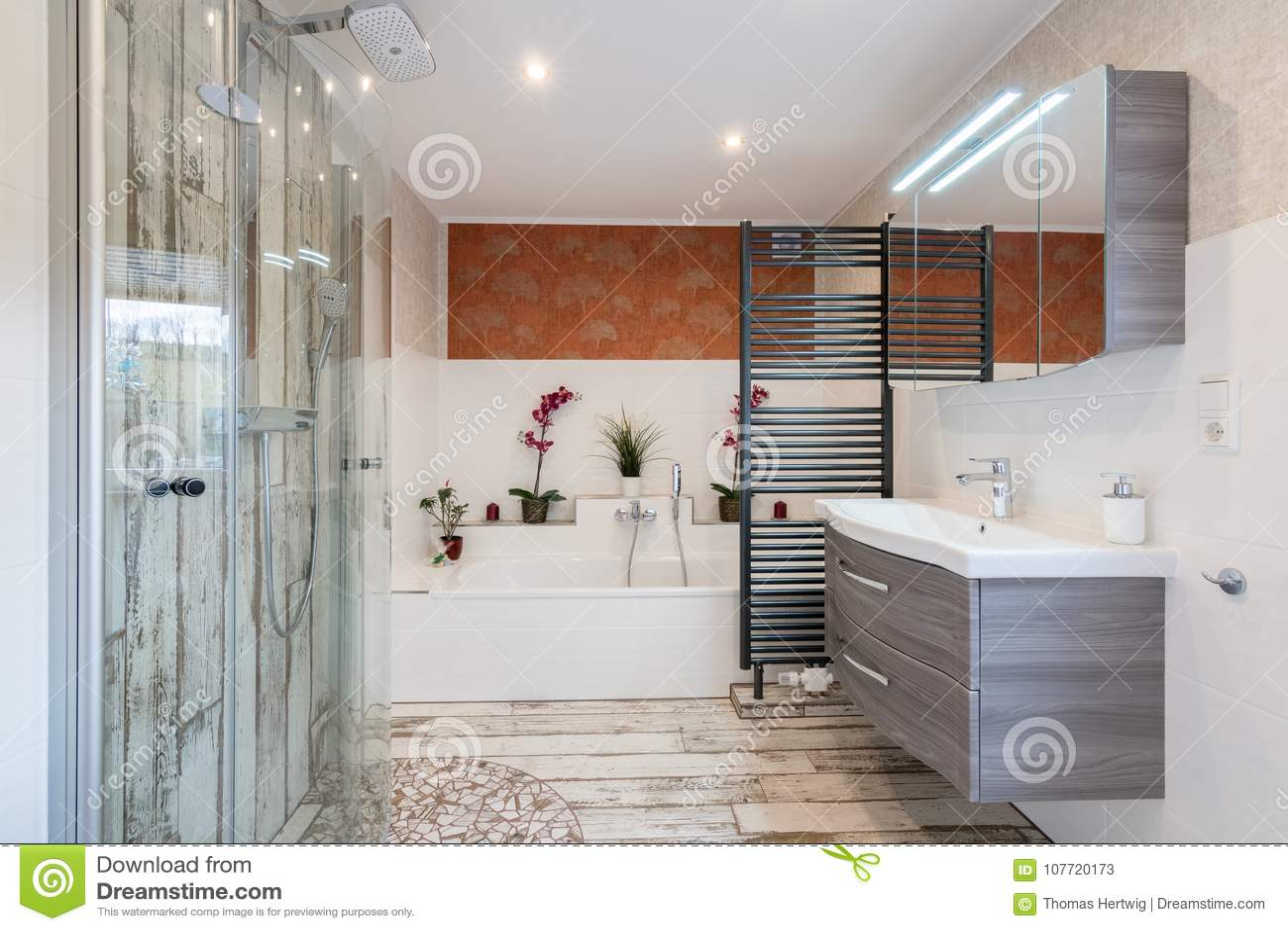 Modern bathroom in vintage style with sink, bathtub, glass shower and black towel dryer